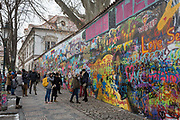 The John Lennon Memorial Wall in Velkoprevorske namestiGrand Priory Square, Malá Strana, on 18th March, 2018, in Prague, the Czech Republic. The Lennon Wall or John Lennon Wall is a wall in Prague, Czech Republic. Once a normal wall, since the 1980s it has been filled with John Lennon-inspired graffiti and pieces of lyrics from Beatles songs. In 1988, the wall was a source of irritation for the communist regime of Gustáv Husák. Young Czechs would write grievances on the wall and in a report of the time this led to a clash between hundreds of students and security police on the nearby Charles Bridge. The movement these students followed was described ironically as Lennonism and Czech authorities described these people variously as alcoholics, mentally deranged, sociopathic, and agents of Western capitalism.