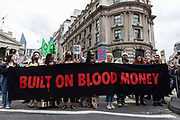 A group of Extinction Rebellion activists wave flags and hold up a banner reading built on blood money as they march through the streets on 27th August, 2021 in London, United Kingdom. The activist group Extinction Rebellion XR are planning actions of disruption for two weeks straight beginning on August 23rd, 2021 in an effort to bring awareness and priority to the global climate emergency in advance of the COP 26 Summit which will be held in Glasgow later this year.