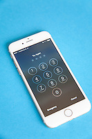 Gold and white Apple iPhone 6 with log in screen for password, against a blue background