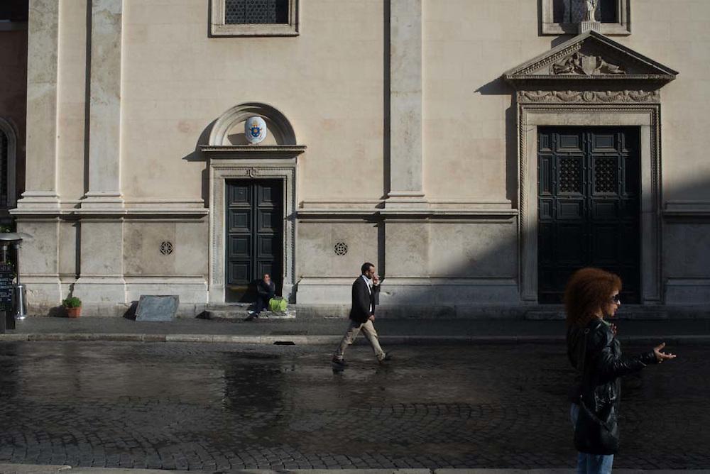 People walk along a street in a plaza in Rome