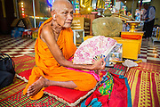 """04 FEBRUARY 2013 - PHNOM PENH, CAMBODIA:  An elderly monk prays during a cremation chanting service for King-Father Norodom Sihanouk at Wat Ounalom (also spelled Wat Onalaom) in Phnom Penh. Norodom Sihanouk (31 October 1922- 15 October 2012) was the King of Cambodia from 1941 to 1955 and again from 1993 to 2004. He was the effective ruler of Cambodia from 1953 to 1970. After his second abdication in 2004, he was given the honorific of """"The King-Father of Cambodia."""" Sihanouk died in Beijing, China, where he was receiving medical care, on Oct. 15, 2012.   PHOTO BY JACK KURTZ"""