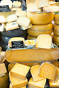 Cheese wheels and wedge on display shelves at traditional cheese shop 't Kaaswinkeltje in Gouda, Holland, The Netherlands