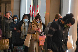 © Licensed to London News Pictures. 30/12/2020. Manchester, UK.  Shoppers wearing face masks queue outside a Zara store in  Manchester City ahead of Tier 4 restrictions come into force. The county of Greater Manchester from Thursday 31 December will move into Tier 4 following a spike in coronavirus cases. Photo credit: Ioannis Alexopoulos/LNP