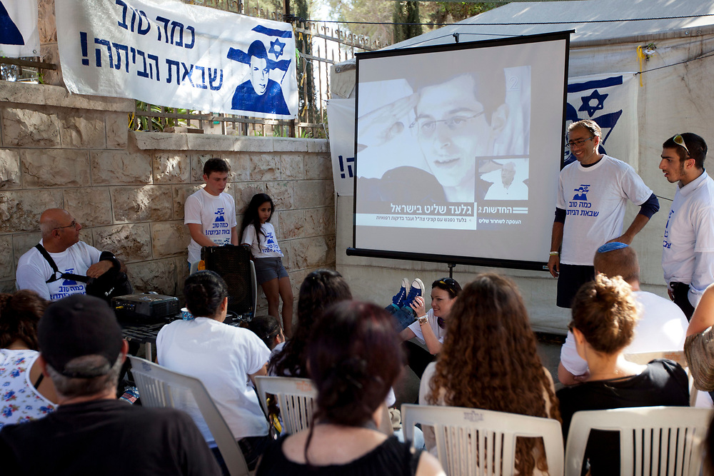 Israelis watch images of Israeli Defense Forces soldier Gilad Shalit on TV following his release on October 18, 2011 outside a protest tent set to call for his release, near Prime Minister Netanyahu's residence in Jerusalem, Israel. Shalit was freed after being held captive for five years in Gaza by Hamas militants, in a deal which saw Israel releasing more than 1,000 Palestinian prisoners.
