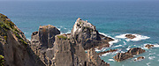 Rocky rugged coastline near Azenha do Mar, Alentejo Littoral, Portugal, southern Europe with white storks ( Ciconia ciconia) nesting on cliffs - the only place in the world where they nest on the coastWaves breaking on dramatic rocky
