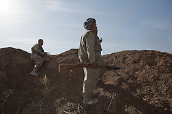 20/10/2016. Bashiqa, Iraq. Peshmerga fighters watch as colleagues fight to retake the ISIS held town of Tiskharab,Iraq , close to Mosul, during an operation to retake areas around the town of Bashiqa from the Islamic State today (20/10/2016).<br /> <br /> Launched in the early hours of today with support from coalition special forces and air strikes, the attack is part of the larger operation to retake Mosul from the Islamic State, and involves both the Kurds and the Iraqi Army. The city of Bashiqa, around 9 miles north of Mosul, is one of several gateway areas that must be taken before any attempted offensive on Mosul itself.<br /> <br /> Despite the peshmerga suffering several casualties after militants fought back using mortars, heavy machine guns and snipers, the Kurdish forces were quickly taking ground with Haider al-Abadi, the Iraqi prime minister, stating that the operation to retake Mosul was progressing faster than expected. Photo credit: Matt Cetti-Roberts/LNP