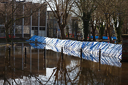 © Licensed to London News Pictures. 16/02/2014. Winchester, Hampshire, UK. One of two flood barriers designed by Geodesign in Sweden in place at Park Avenue in Winchester, Hampshire. Work is well underway by Hampshire Fire & Rescue and the Environment Agency to restore the flooded areas back to normality. Photo credit : Rob Arnold/LNP