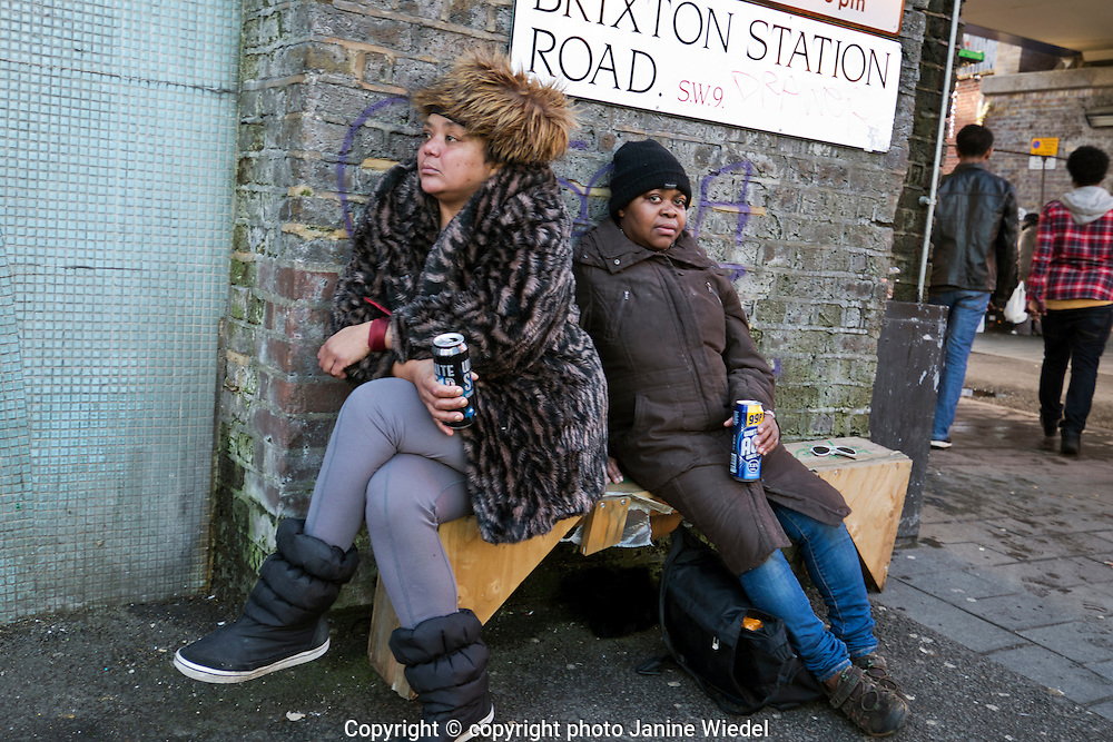 Two women sitting in the street in Brixton South London resting and having a drink