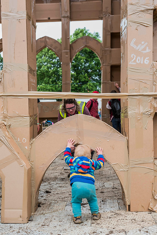 A young boy is very Curious. Cardboard boxes are turnetd into bricks with messages on them, to re create the Glastonbury Tor. The project is the idea of a french artist. The Circus Field - The 2016 Glastonbury Festival, Worthy Farm, Glastonbury.