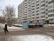 Frau mit hohen Absaetzen vor einem Plattenbau. Strassenszene im Zentrum der sibirischen Hauptstadt Nowosibirsk.<br /> <br /> Woman with high heels  in front of a panel house. Street scene in the center of the Sibirian capital Novosibirsk.