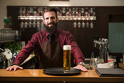 Portrait of young man at bar counter with glass of beer in tray