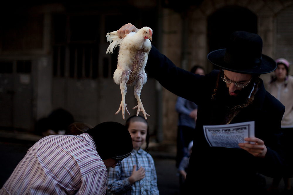 An ultra-Orthodox Jewish man swings a chicken, later to be slaughtered, over the head of his wife as part of the Kaparot ritual, ahead of the Jewish holiday of Yom Kippur in the neighborhood of Mea Shearim on September 15, 2010. Kaparot is a ritual connected to Yom Kippur, where chickens are slaughtered as a symbolic gesture of atonement, it is believed that one transfers one's sins from the past year into the chicken.