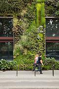 Pedestrians walk past the Musee du Quai Branly, where plants grow up the exterior walls, in Paris, France