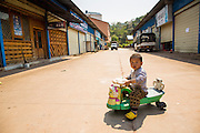 13 MARCH 2013 - ALONG HIGHWAY 13, LAOS: A boy rides his toy bike in the Chinese market near the end of Highway 13 in the Boten Special Economic Zone. The SEZ is in Laos immediately south of the Lao Chinese border. It has turned into a Chinese enclave but many of the businesses struggle because their goods are too expensive for local Lao to purchase. Some of the hotels and casinos in the area have been forced to close by the Chinese government after reports of rigged games. The paving of Highway 13 from Vientiane to near the Chinese border has changed the way of life in rural Laos. Villagers near Luang Prabang used to have to take unreliable boats that took three hours round trip to get from the homes to the tourist center of Luang Prabang, now they take a 40 minute round trip bus ride. North of Luang Prabang, paving the highway has been an opportunity for China to use Laos as a transshipping point. Chinese merchandise now goes through Laos to Thailand where it's put on Thai trains and taken to the deep water port east of Bangkok. The Chinese have also expanded their economic empire into Laos. Chinese hotels and businesses are common in northern Laos and in some cities, like Oudomxay, are now up to 40% percent. As the roads are paved, more people move away from their traditional homes in the mountains of Laos and crowd the side of the road living off tourists' and truck drivers.    PHOTO BY JACK KURTZ