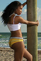 A young african american observes the sunrise in the beach.