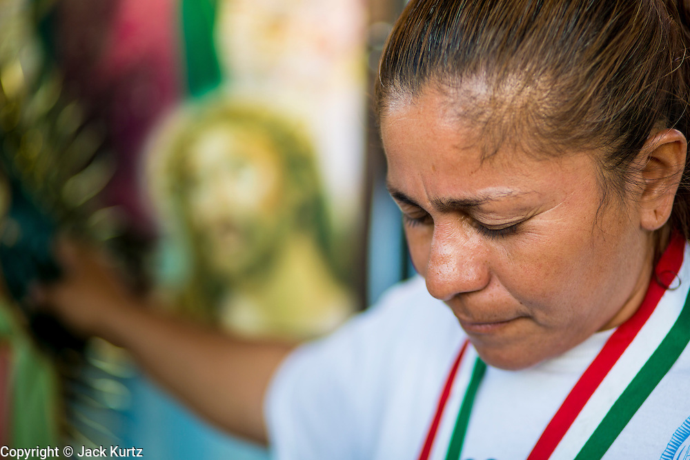 25 JUNE 2012 - PHOENIX, AZ:  GEORGINA SANCHEZ, prays at an impromptu alter at the Arizona State Capitol in Phoenix, AZ, Monday. The lawsuit, US v. Arizona, determines whether or not Arizona's tough anti-immigration law, popularly known as SB1070 is constitutional. Among other things, the law requires police officers to check the immigration status of anyone whom they arrest, allows police to stop and arrest anyone whom they believe to be an illegal immigrant, makes it a crime for someone to be in the state without valid immigration papers, and makes it a crime to apply for or hold a job in Arizona without proper papers. The federal government sued Arizona because it believes the law is invalid because it is trumped by federal immigration laws. The court struck down most of the law but left one section standing, the section authorizing local police agencies to check the immigration status of people they come into contact with.   PHOTO BY JACK KURTZ