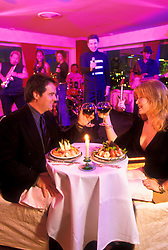Stock photo of a couple seated at a table in front of the band playing live at a restaurant