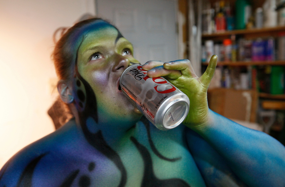 """Gabi Jones drinks a soda during a break from being painted by airbrush artist David Brawner as a piece of """"bodyart"""" in a garage studio in a Denver suburb April 13, 2010.  Jones (not her real name) at 502 pounds is a size acceptance advocate who says she wanted to be painted """"...to push the envelope on what a big person can do and break the molds of what is accepted in society.""""  REUTERS/Rick Wilking  (UNITED STATES)"""