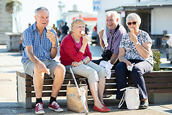 © Licensed to London News Pictures . 13/09/2019. Bournemouth, UK. A group of tourists eat ice creams on the promenade by the beach in Bournemouth as a late summer heatwave brings high temperatures to the south coast of England . Photo credit: Joel Goodman/LNP
