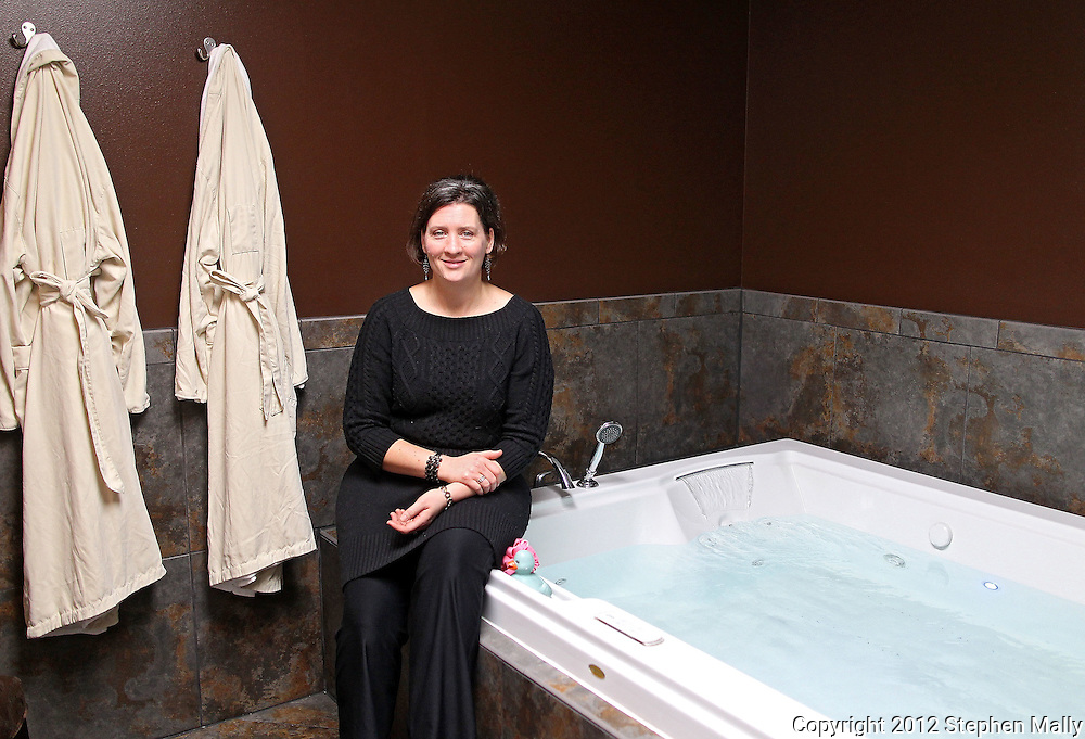 Owner Wahneta Dimmer sit on the edge of the two person jacuzzi hot tub at Hands in Harmony, 2701 1st Ave SE #104, in Cedar Rapids on Tuesday, March 6, 2012. (Stephen Mally/Freelance)