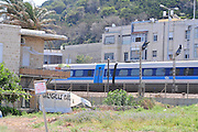 Israel, Haifa, Israeli Rail Train speeds past houses