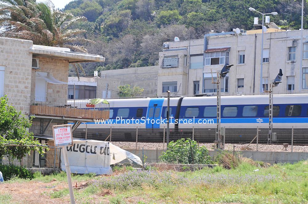 Israel, Haifa, Israeli Rail Train speeds past houses