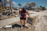 Brandy Wood Jessen recovering a painting from the Driftwood Inn in  Mexico Beach, Florida that was badly damaged by Hurricane Michael.