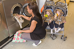 Mother using launderette with twins in buggy. (This photo has extra clearance covering Homelessness, Mental Health Issues, Bullying, Education and Exclusion, as well as the usual clearance for Fostering & Adoption and general Social Services contexts,)