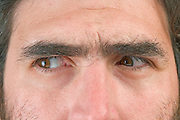 close up of a man's face with his eyes looking to the left