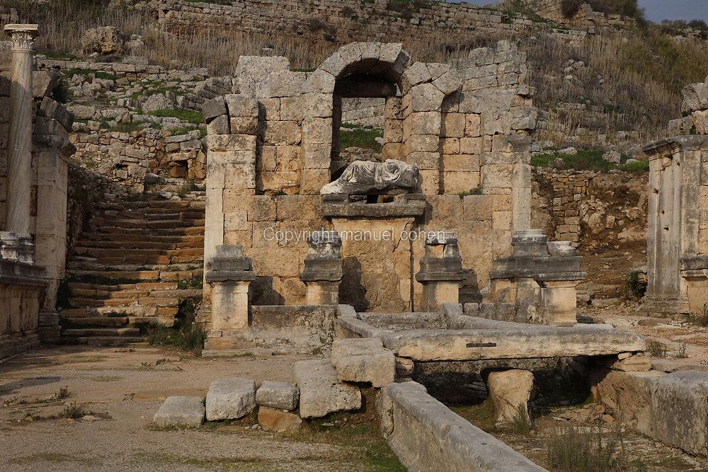 Nymphaion of Kestros, a monumental fountain under the acropolis, at the end of the colonnaded main street, in Perga, an ancient Pamphylian city ruled by the Persians, Greeks and Romans, in Antalya, Turkey. The limestone nymphaion gate complex is U-shaped and 2 storeys high, accessed via 2 passages covered by slab vaults. The fountain has a triple-arched central niche with a reclining sculpture of the river god Kestros. In the foreground is the open water channel along the centre of the main street, which is fed by the fountain. Picture by Manuel Cohen