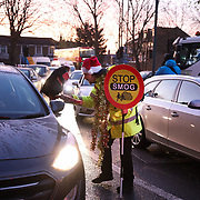 The activist group Stop Killing Londoners block access roads out of Chiswick Roundabout, December 18th 2017, London, UK.  Liam handing out mince pies explaining drivers about the action and keeping the Christmas peace. The action is part of a long running campaign to curb air pollution in London.
