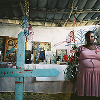 A woman stands in front of her altar in Las Guanabanas, Dominican Republic. The altar has saints images and offerings related to Religión Popular.