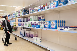 © Licensed to London News Pictures. 21/09/2020. London, UK. A customer buys toilet paper from virtually empty shelves at a Sainsburys supermarket in Alperton, North West London. Some shoppers have been reported to start panic buying items including toilet paper and household good ahead of a feared second wave of Covid-19. Photo credit: London News Pictures