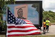 Jerred Lewis, 9, and Charolyn Lewis ready to take a picture in front of a slideshow of images of George Floyd outside of Fountain of Praise church at the public memorial for George Floyd in Houston, TX Monday June 8.