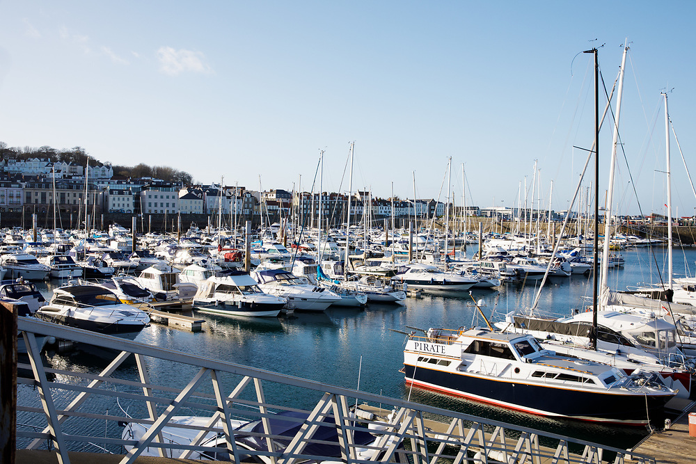 Fishing boats and yachts moored up in low sunlight at the harbour in Guernsey, Channel Islands
