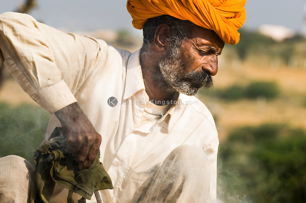 A adult man winces from smoke getting in his eyes while making a ravanatha instrument for tourists at the Pushkar mela, Rajasthan, India.