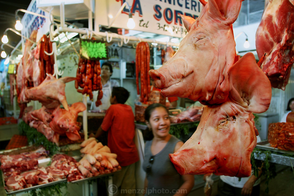 In what may be a disappearing custom, shoppers throng Cuernavaca, Mexico's daily public market, inspecting the alarmingly fresh meat (the hogs' heads in this image signal the presence of a butcher) and picking up snacks at the many small restaurants inside. Hungry Planet: What the World Eats (p. 224). This image is featured alongside the Casales family images in Hungry Planet: What the World Eats.