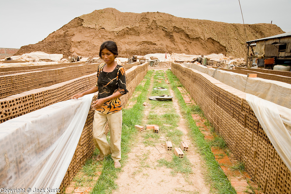30 JUNE 2006 - PHNOM PENH, CAMBODIA: A woman uncovers bricks that have been drying in the sun at a brick factory in Phnom Penh, Cambodia. After the bricks are dried in the sun, they are baked in a kiln for seven days. According the United Nations Food and Agricultural Organization, there are more than 70 brick factories in Phnom Penh and its environs. Environmentalists are concerned that the factories, most of which burn wood in their kilns, contribute to deforestation in Cambodia. They are encouraging factory owners to switch to burning rice husks, as brick kilns in neighboring Vietnam do. The brick factories are kept busy feeding Phnom Penh's nearly insatiable appetite for building materials as the city is in the midst of a building boom brought by on economic development and the need for new office complexes and tourist hotels.   Photo by Jack Kurtz / ZUMA Press