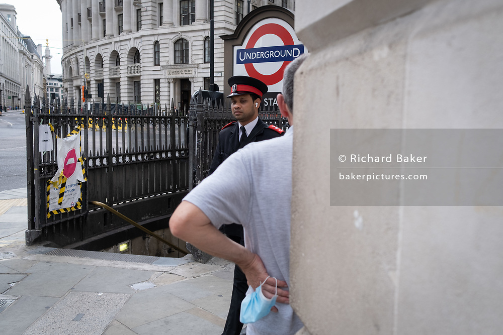A security guard passes a man holding, but not wearing his face covering during the Coronavirus pandemic at Bank Station in the City of London, the capital's financial district, on 6th August 2020, in London, England.