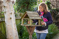 Feeding the birds - putting seed out onto the bird table