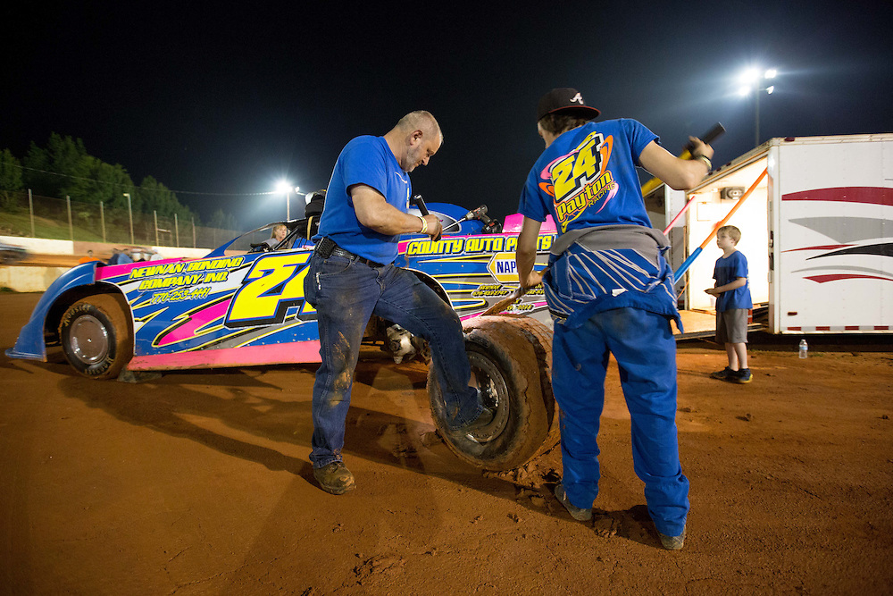 May 10, 2014; Senoia, GA, USA; Jimmy Ferrell (left) and Corey Payton scrape mud off a tire for Payton's race car at Senoia Raceway. Mandatory Credit: Kevin Liles-USA TODAY Sports