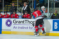KELOWNA, CANADA - APRIL 8: Caleb Jones #3 of the Portland Winterhawks checks Kole Lind #16 of the Kelowna Rockets into the boards in front of the bench on April 8, 2017 at Prospera Place in Kelowna, British Columbia, Canada.  (Photo by Marissa Baecker/Shoot the Breeze)  *** Local Caption ***
