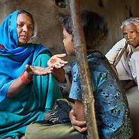 "Sehrulnisa at home with her youngest son Akhtar Ali, 9, and husband Barqat Ali, 55. ..Sehrulnisa, 45, has 12 children. A Muslim resident of Deramunshi village, she is an active member of the AROH campaign. In 2007, Sehrulnisa's husband attempted to sell the family's six bigha of land ((one bigha = 1,300 sq metre) . Upon discovering this, Sehrulnisa met the local subdivisional magistrate, informed him that the sale threatened the wellbeing of her family and successfully prevented the sale. Sehrulnisa explains that, had the sale had gone ahead, ""my children would have had to go to work and I would have had to take them out of school. Families who don't have agricultural land are basically day-wage labourers; many live in dire conditions, with torn clothes."" Sehrulnisa's own experience has informed her position as an advocate for the rights of women, ""I cook the food; go to the field with my husband I have to do work; look after the children, take care of their education; so why shouldn't women have their rights to the land protected if they do all of this?""..In the north Indian state of UP (Uttar Pradesh), women are responsible for 70 to 80 percent of agricultural work but their contribution remains neglected at all the levels: family, social, economic and policy. Over three quarters of UP's households are involved in farming of which 91% percent operate on land that is marginal and small. Small and marginal farmers often lack access to major agricultural services, such as credit, extension, insurance, and markets...On October 15, 2005 a movement called AROH was launched campaigning for the recognition of women as farmers. A federation of women farmers popularly known as ""Aroah Mahila Kissan Manch"" has been formed in all the districts of Uttar Pradesh. AROH has begun lobbying the UP government for women to be registered as joint owners - with their husbands - of land. At present only 6.5% of women own land in UP. AROH encourages women's co-operatives and other forms o"