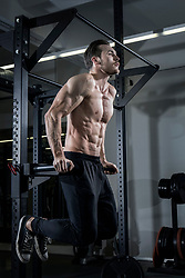 Shirtless muscular man doing dips exercise at the gym