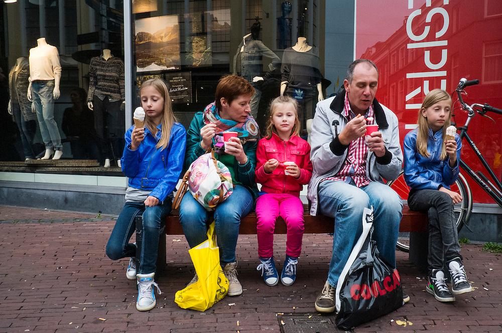 Nederland, Arnhem, 6 okt 2013<br /> Familie met 3 dochters eten ijsje na het winkelen op een bankje in winkelstraat.<br /> Family eating an icecream after shopping.<br /> Foto(c): Michiel Wijnbergh