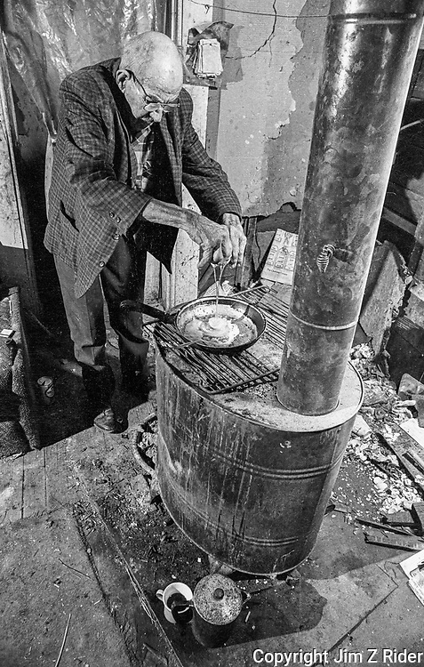 Orville L. May cooks breakfast on a wood-burning stove in his modest home on Pigeon Hill in Bloomington, Indiana.  Orville, who was content with poverty, spent his days smoking a pipe, drinking beer, chopping wood, and collecting rain water from his gutters. His daughter offered to take him in but Orville didn't want to leave the drafty shack he called home.