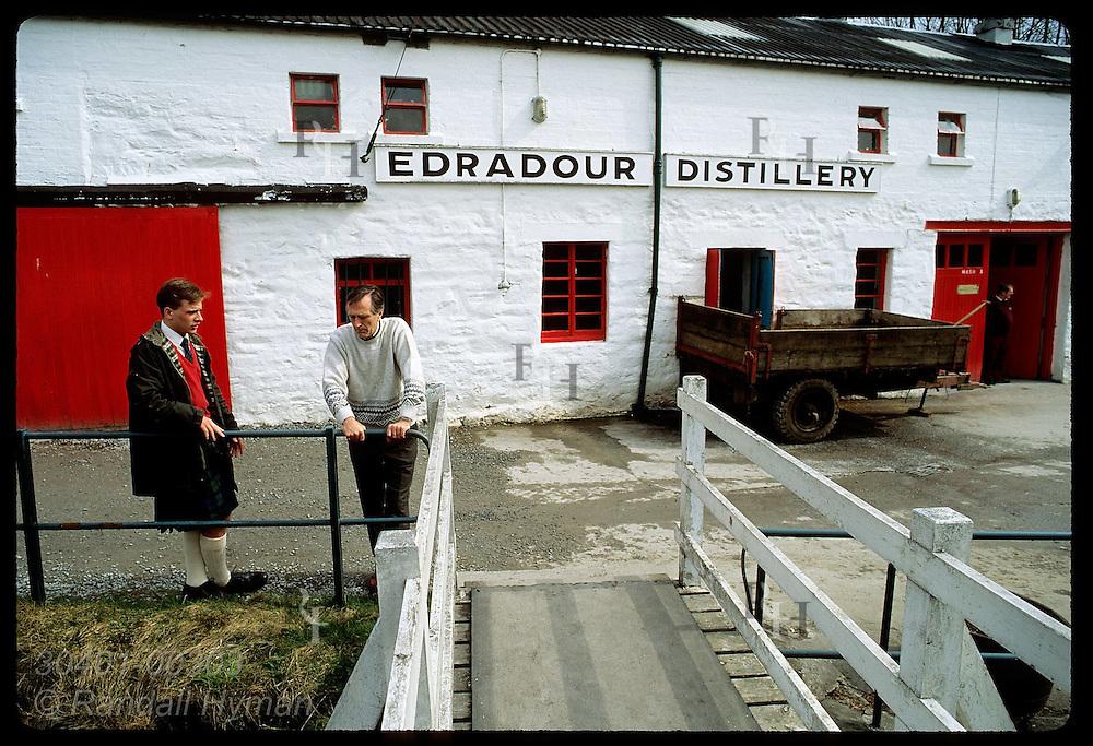 Distillery workers talk outside Edradour stillhouse,Scotland's smallest distillery; Pitlochry. Scotland