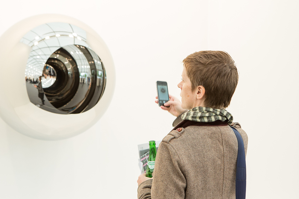 """New York, NY - 6 May 2016. Frieze New York art fair. A woman taking a photo of """"Alice - Circle"""", a stanless steel sculpture by Anish Kapoor in the Lisson Gallery."""