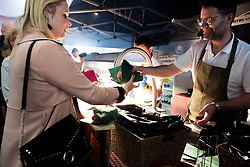 Raceoers buy food from the food stalls at Cheltenham Racecourse