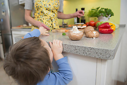 Boy peeping while mother cutting vegetables